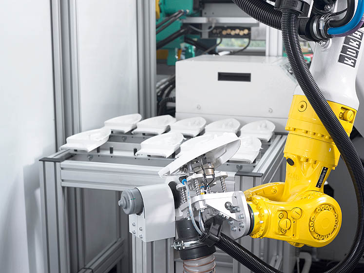 Thanks to its 3-D movements, the six-axis robotic system is fully free in its parts handling, for example during the removal of flash from external contours of insulating rails for ironsLSR injection moulding